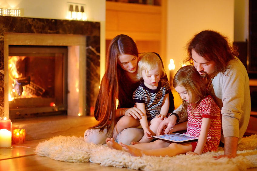 family enjoying warmth of fireplace
